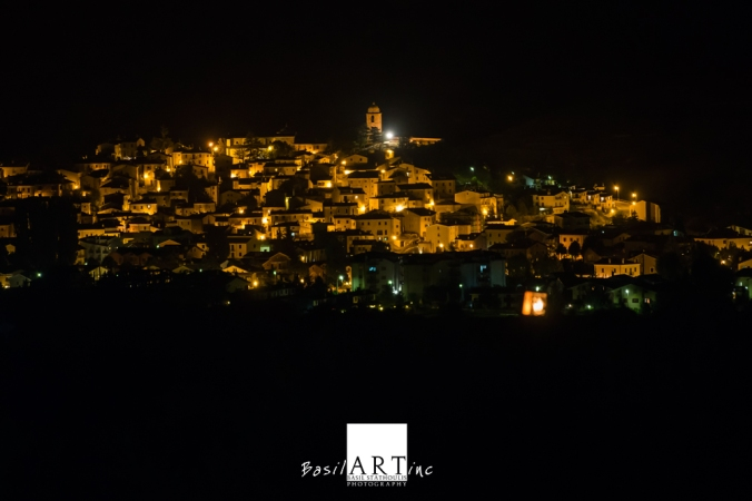 View of Rocca di Mezzo by night withe Punto do Riferimento next to the bell tower