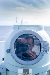 Self-portrait in the glass of the ship's compass. Just thinking.