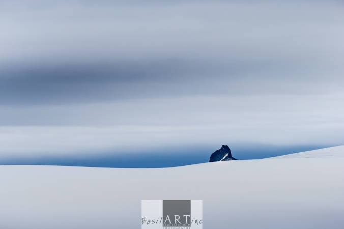 Black blue land on the horizon Swallows a single stony peak